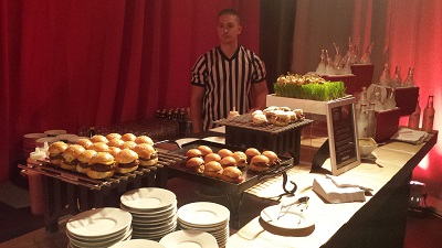 The food attendants had on sports-themed attire, such as referee uniforms and football jerseys.